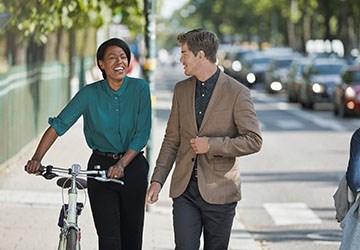 Mann und Frau mit Fahrrad draussen, auf dem Weg zu einem Vorstellungsgepräch