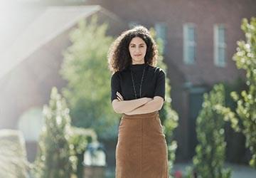 Frau blickt entschlossen und zufrieden, beflügelt von der Unterstützung eines Mentorenprogrammes