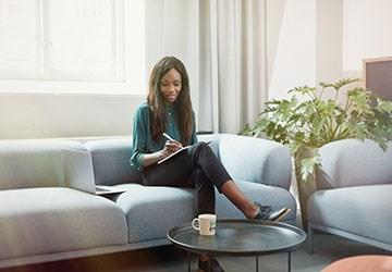 Frau sitzt im Büro und schreibt Ihren Lebenslauf