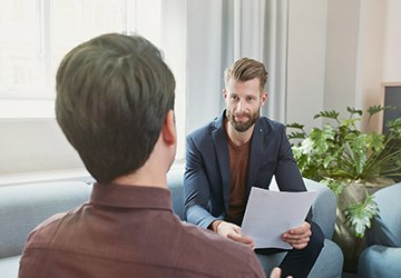 Recruiter stellt Bewerber in einem Job-Interview Fragen