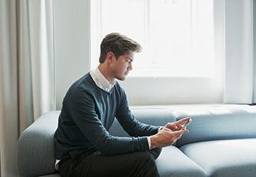 Mann sitzt auf der Couch und schaut auf seinem Telefon nach neuen Stellenanzeigen