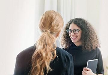 Zwei Frauen schütteln die Hände in Folge beantworteter Fragen zur Jobsuche
