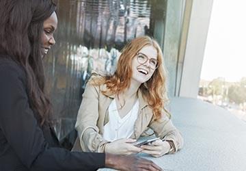 Bewerberinnen lächeln und freuen sich über einen erfolgreichen Bewerbungsprozess
