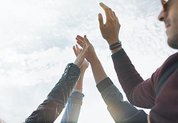 Hände von erfolgreichen Bewerbern die durch Personalvermittlung vermittelt wurden in der Luft